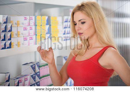Woman Examining Medicine At Pharmacy