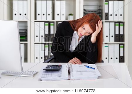 Tensed Businesswoman With Calculator And Binder At Desk