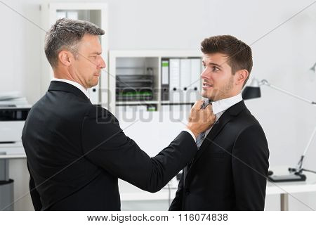 Mature Businessman Gripping Employee's Tie