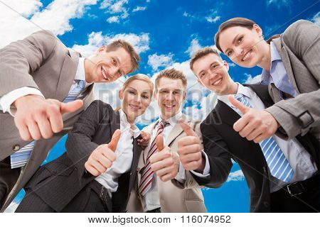 Confident Business Team Showing Thumbs Up Against Sky
