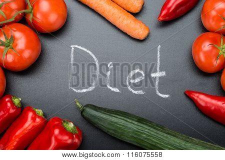 Diet Written Amidst Fresh Vegetables On Blackboard