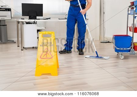 Janitor Cleaning Floor With Mop In Office