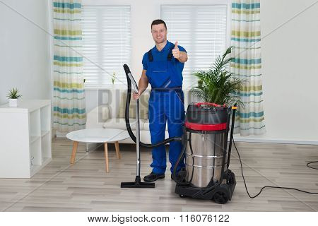 Janitor Showing Thumbs Up While Holding Vacuum Cleaner At Home