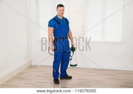 Smiling Male Worker Holding Pesticide Container At Home