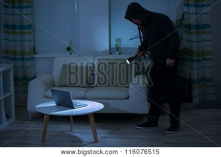 Robber Holding Flashlight Over Laptop At Home