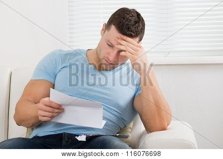 Upset Man Reading Letter On Sofa At Home
