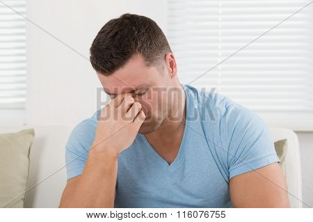 Man With Headache Pinching His Nose On Sofa