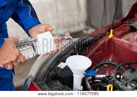 Worker Pouring Water Into Windshield Water Tank