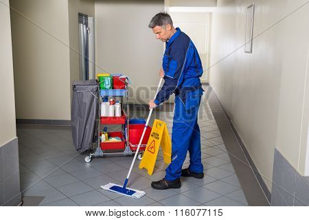 Male Worker With Broom Cleaning Corridor