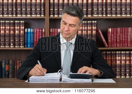 Accountant Writing On Document While Using Calculator At Table