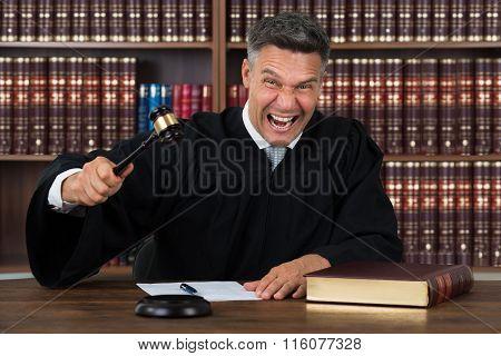 Angry Judge Striking His Gavel At Table