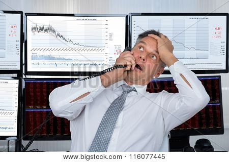 Sad Stock Trader With Hand On Head Using Telephone