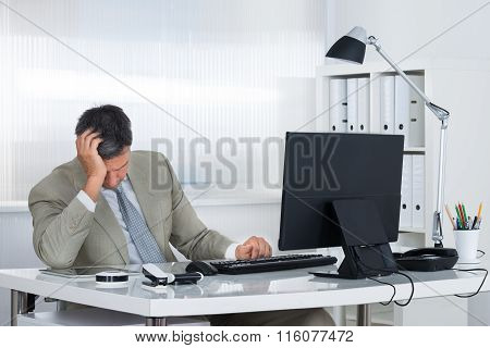 Tired Businessman Leaning Head On Hand At Desk