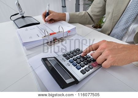 Accountant Calculating Bills In Office