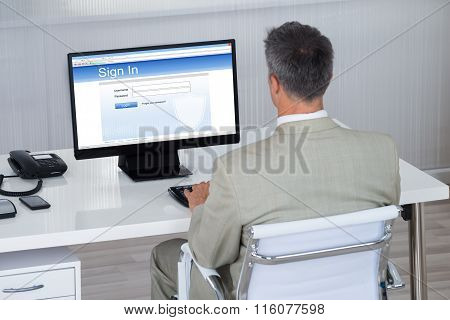 Businessman Signing Into Website At Desk In Office
