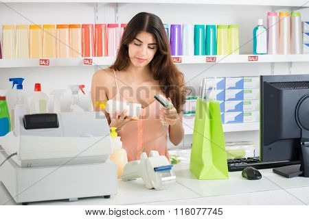 Saleswoman Scanning Product At Checkout Counter In Store