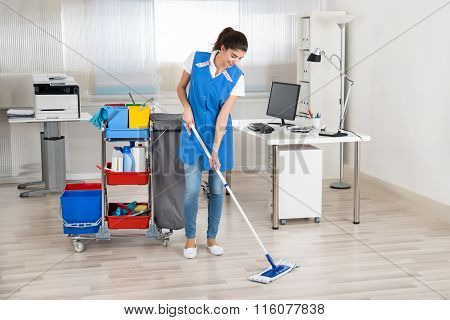 Happy Female Janitor Mopping Floor In Office
