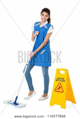 Happy Janitor Mopping By Caution Wet Floor Sign
