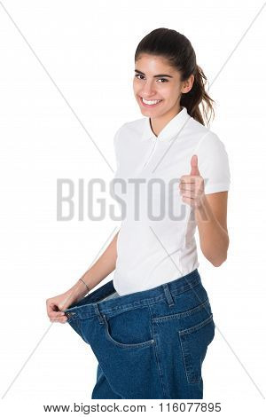 Smiling Woman Showing Her Old Jeans After Successful Diet
