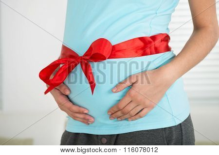 Pregnant Woman With Red Ribbon Tied To Stomach