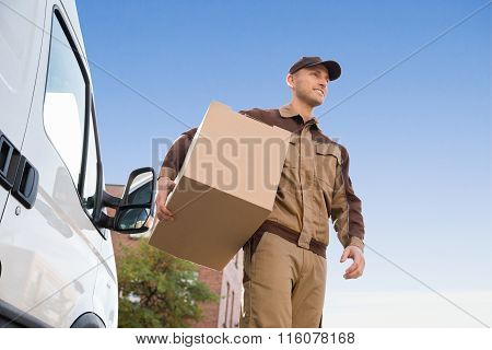 Delivery Man Carrying Cardboard Box Against Sky