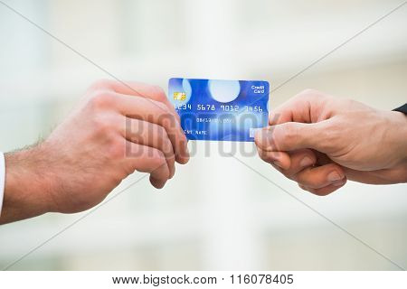 Businessmen Holding Credit Card Together