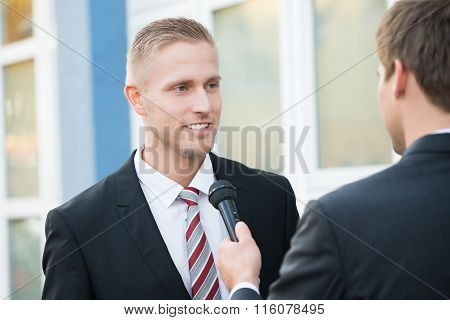 Journalist Taking Interview Of Smiling Businessman