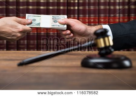 Gavel On Table With Judge Taking Bribe From Businessman