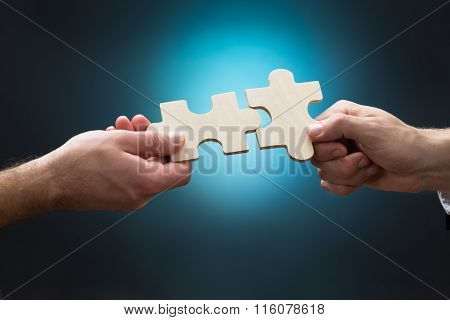 Closeup Of Businessmen Joining Jigsaw Pieces