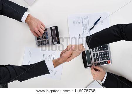 Businessmen Shaking Hands While Calculating Finance At Desk