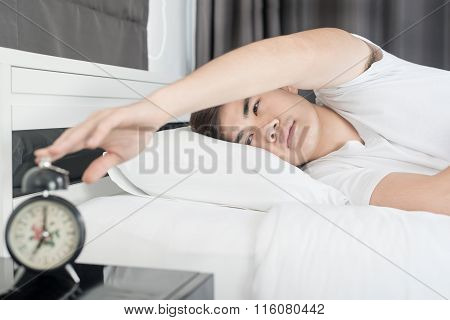 Asian Man Lying On The Bed And Stopping Alarm Clock