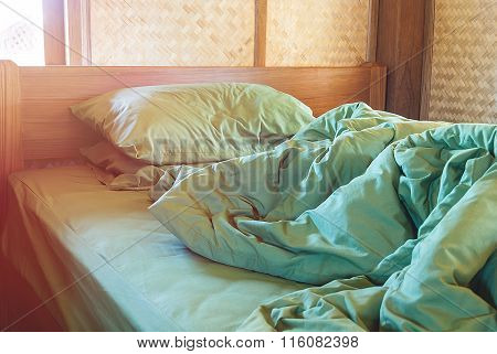 Green Pillow And Blanket With Wrinkle Messy On Bed In Vintage Wooden Bedroom With Lighting Upper Lef
