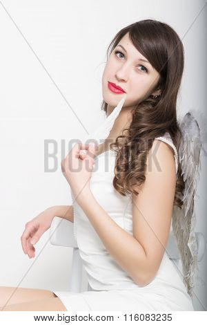 Beautiful sexy slim woman in a little white dress with wings behind her