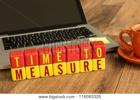 Time To Measure written on a wooden cube in a office desk