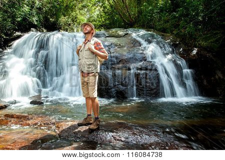 Hiker Standing In Front Of A Waterfall