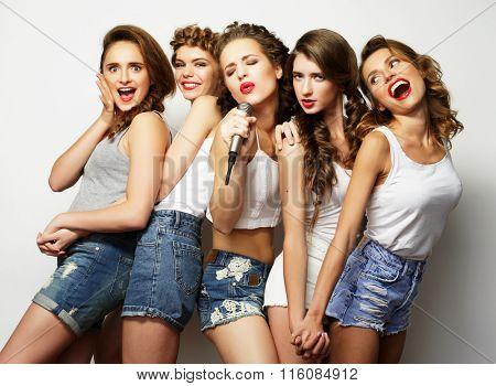 beautiful stylish hipster  girls singing karaoke