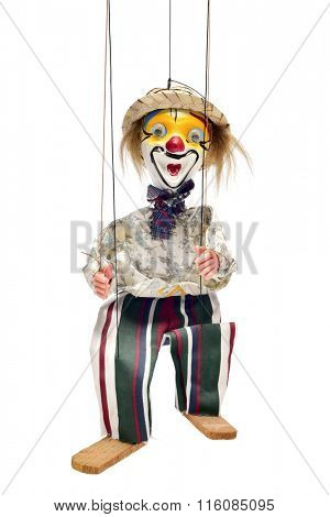 an old marionette with its face painted like a clown being manipulated against a white background
