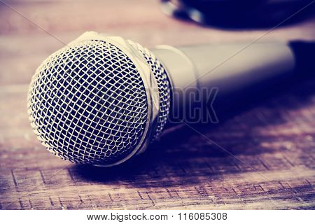 a microphone on a rustic wooden surface, with a filter effect
