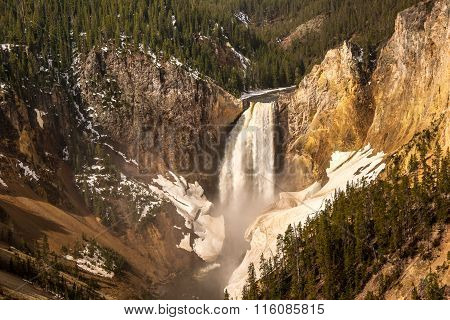 Spring run-off cascades over the lower falls of the yellowstone River with ice and snow along the canyon.