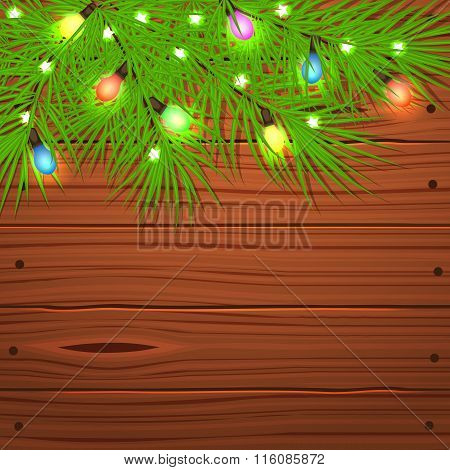 Christmas tree branches and light bulb on wooden.