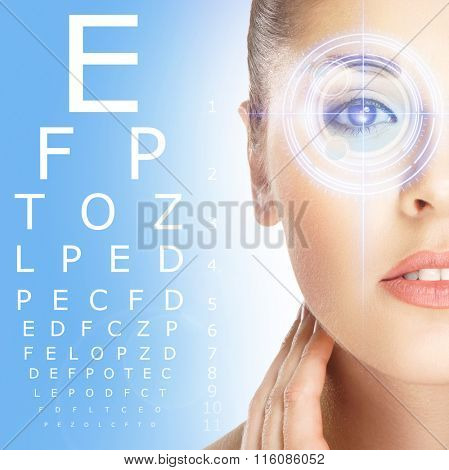 Close-up of woman with laser optometry over blue background.