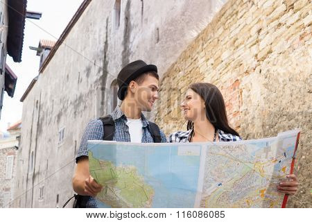 Tourists exploring the map on old baroque street.
