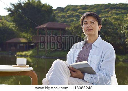 Man Reading At Waterside In Morning