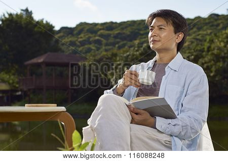 Man Reading Outdoor With Coffee In Hand
