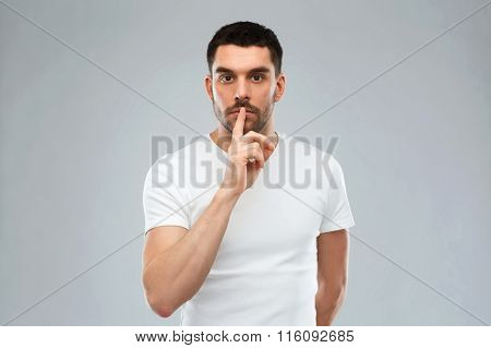 young man making hush sign over gray background