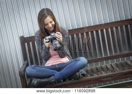 Young Girl Photographer Sitting on Bench Looking at Back of Camera.