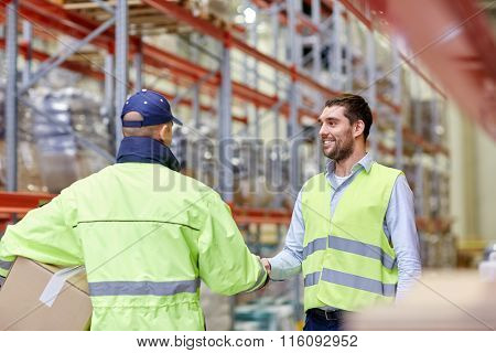 men in safety vests shaking hands at warehouse