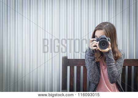 Girl Photographer Sitting On Bench and Pointing Camera.