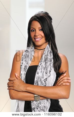Portrait of millennial African American businesswoman smiling with arms crossed