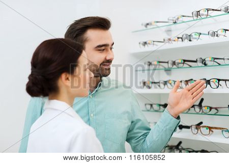 optician and man choosing glasses at optics store
